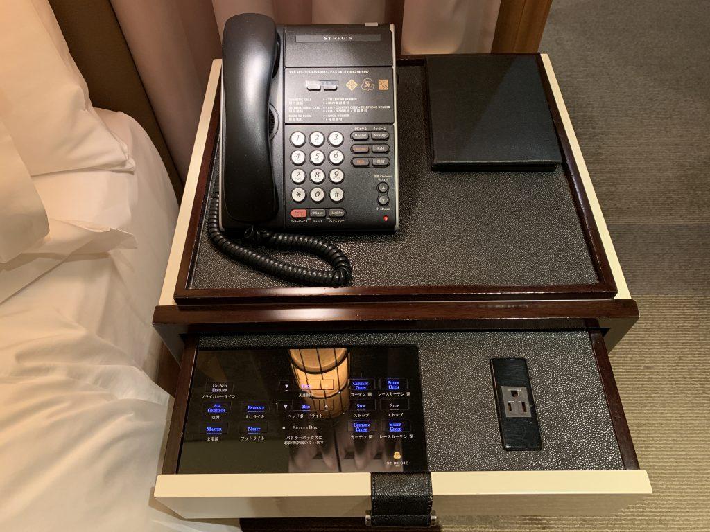 大阪瑞吉酒店-電話,而將床邊桌抽屜拉出,可見到插座及可控制窗簾收合、調節燈光明亮度等的觸控式面板