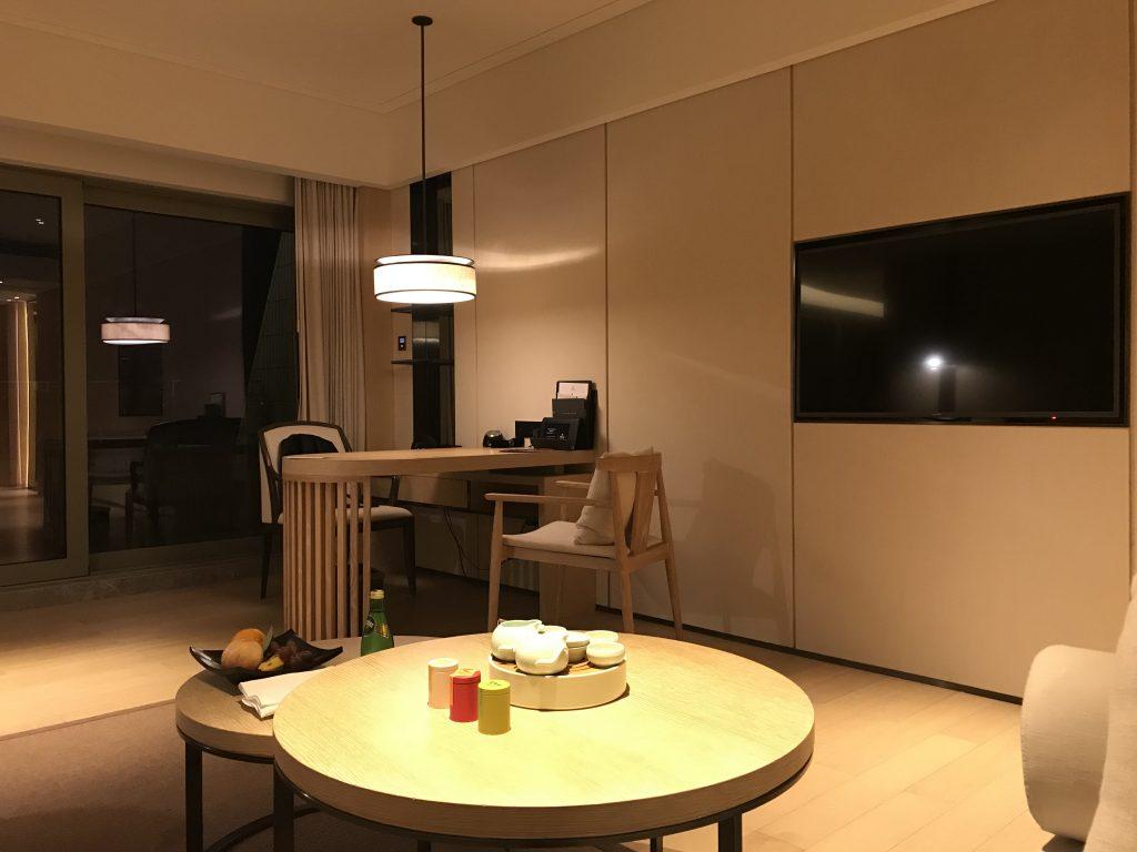 深圳蛇口希爾頓南海酒店-客廳桌子有三盒額外收費的茶葉和沖茶工具,而對面是書桌和電視