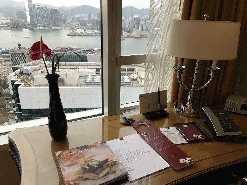 香港港麗酒店-房間書桌上有各式酒店設施小冊子、原子筆、檯燈及電話