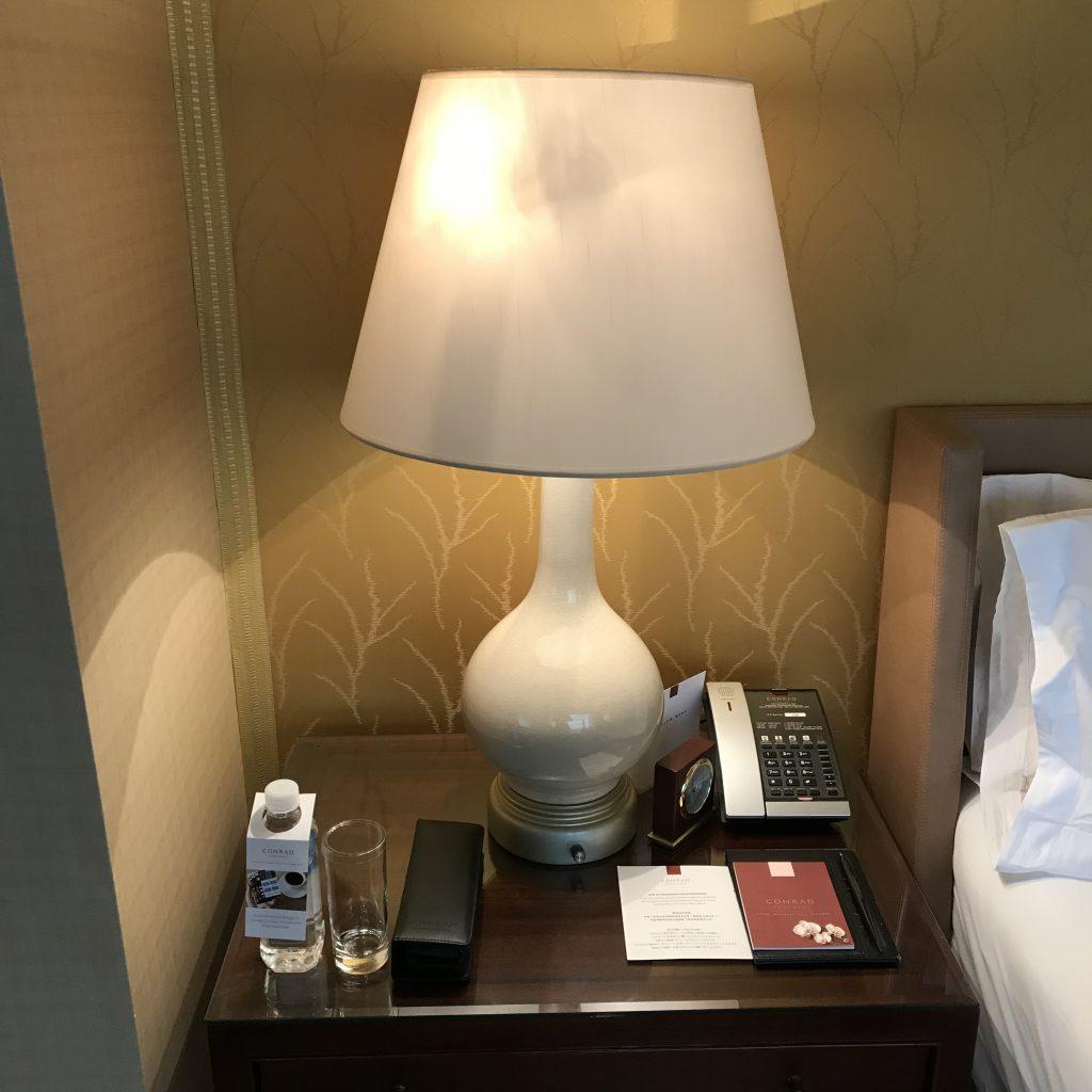 香港港麗酒店-床邊桌有免費樽裝水、床頭燈、文具、鬧鐘及電話
