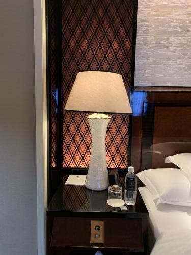 床褥左邊床頭櫃有床頭燈、鬧鐘、免費樽裝水和玻璃水杯