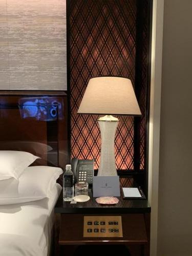 床褥右邊床頭櫃有床頭燈、電話、免費樽裝水、玻璃水杯和文具